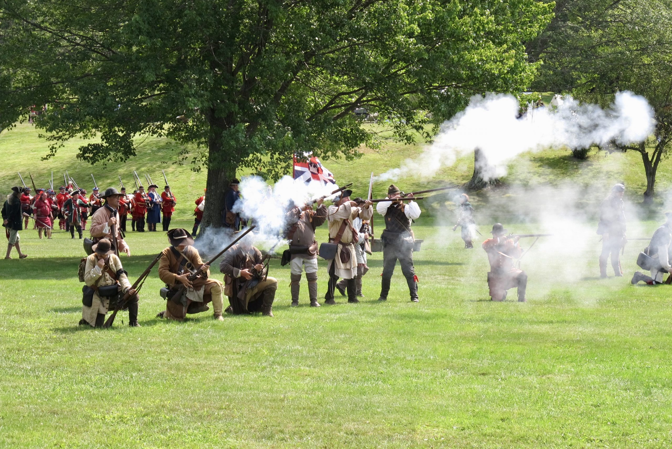 18th Century Colonial troops fire muskets at reenactment